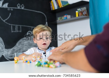 Cute little playfull toddler boy at child therapy session. Private one on one homeschooling with didactic aids. #734585623