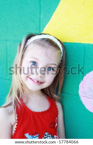 Cute little preschool age girl stands outside a school building waiting to attend school.