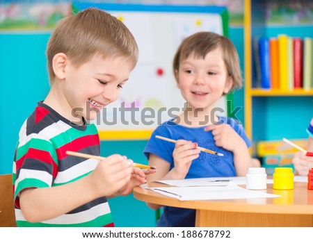 Cute little preschool children drawing with colorful paints at kindergarten