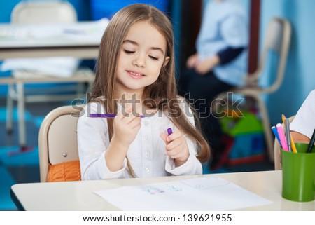 Cute little preschool girl looking at sketch pen in classroom - stock photo
