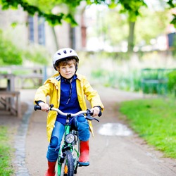 Cute little preschool kid boy riding on bicycle in park. Child in helmet, yellow rain coat and red rubber boots having fun on raine day on bike during rain.