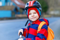 Cute little preschool kid boy riding on scooter riding to school. children activities outdoor in winter, spring or autumn. funny happy child in colorful fashion clothes and with helmet. High speed.
