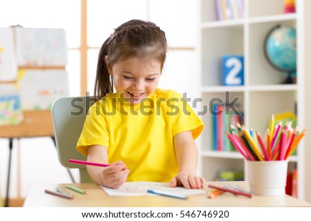Cute little preschooler child girl drawing at home stock photo