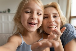 Cute little preschooler girl and young mother have fun make self-portrait picture on camera together, overjoyed mom and small daughter smile laugh take selfie, play enjoy family weekend at home