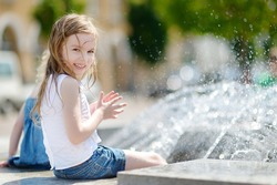 Cute little preschooler girl playing with a city fountain on hot and sunny summer day