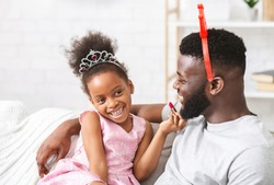 Cute little princess black girl putting lipstick on her queen father. Young father enjoying time with child at home