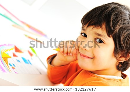 Cute little schoolboy drawing an house and looking at camera