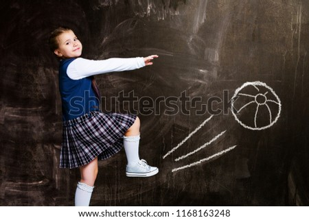 cute little schoolgirl against chalkboard, kicking an imaginary drawn ball