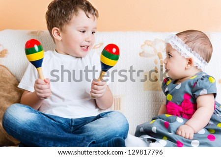 Cute little sister and her brother sitting with maracas on sofa