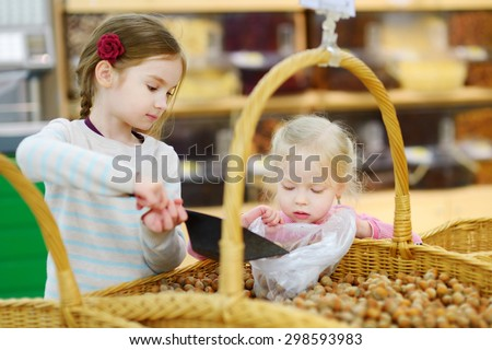 Cute little sisters buying hazelnuts in a food store or a supermarket