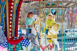 Cute little sisters enjoying spring in funfair: they riding on colorful carousel and looking at camera with wide smiles