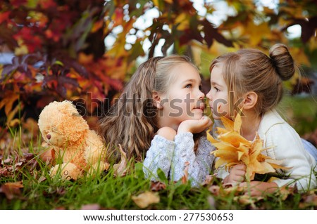Cute little sisters hugging and kissing in autumn park #277530653
