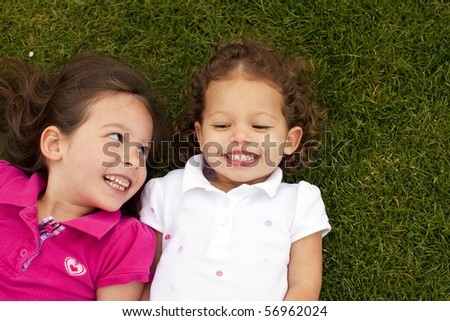 Cute little sisters laying in grass
