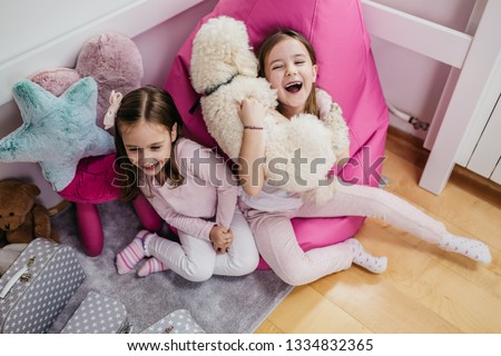 Cute little sisters playing with poodle in children's room.