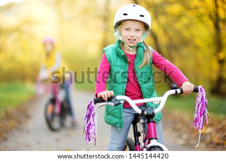 Cute little sisters riding bikes in a city park on sunny autumn day. Active family leisure with kids. Children wearing safety helmet while riding a bicycle. #1445144420