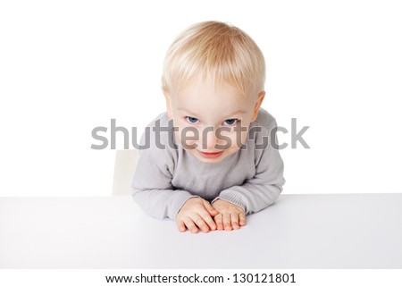 Cute little smiling boy sitting at table isolated on white background