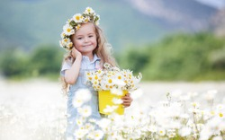 Cute little smiling girl in chamomile field. Little blond child girl with wreath on head in chamomiles