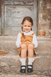 Cute little smiling shy girl with  and sitting on a ladder bench next to old house. Close up portrait of happy three years old child with two blonde pigtails. Rustic, vintage outfit.