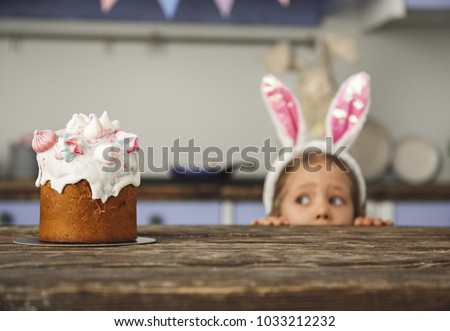 Cute little sweet tooth in bunny ears headband peeking out from behind kitchen table and looking at tasty easter cake with interest. Focus on pastry
