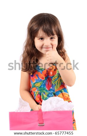 Cute little three year old girl with thumbs up holding a pink shopping back on a white background