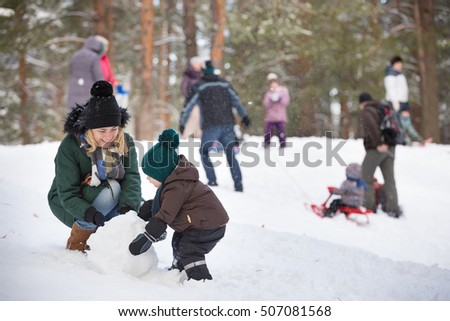 Cute little toddler boy and his mother playing with snow and making snowman. Child having fun outdoors in winter.