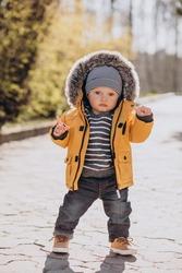 Cute little toddler boy in yellow jacket in park