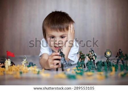 Cute little toddler boy, playing at home with soldiers and figurine toys, playing wars and peace