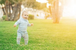 Cute little toddler child making his first step. Learning to walk concept. Goes by himself. Green grass and sunset