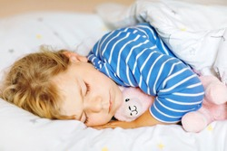 Cute little toddler girl sleeping in bed with favourite soft plush toy lama. Adorable baby child dreaming, healthy sleep of children by day.