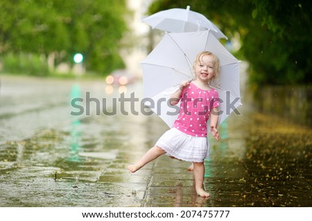 Cute little toddler girl standing in a puddle holding umbrella on a rainy summer day #207475777