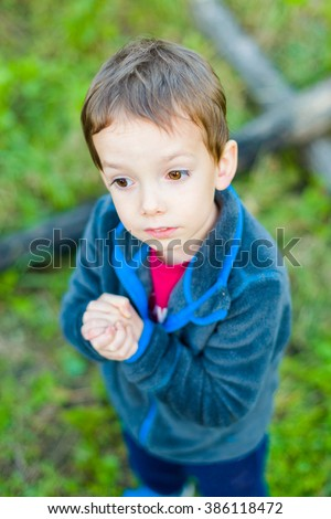 Cute little toddler holding his hands and praying on grass. #386118472