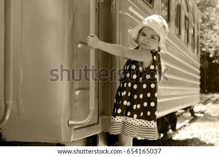 Cute little traveler girl in vintage dress and a hat goes up a train on railway platform, summer outdoor, vacation and traveling concept, retro style