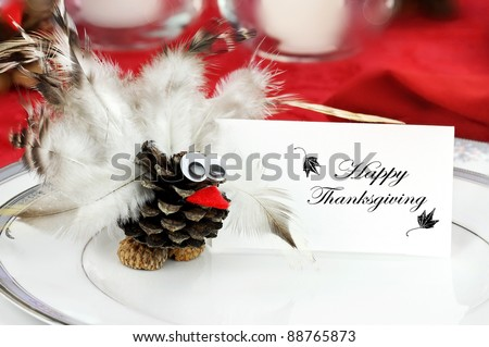 Cute little turkey sits by a place card  on a holiday table for Thanksgiving Day. - stock photo