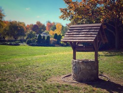 cute little water well wishing well made of stone with a wooden top in a field in autumn in New England Massachusetts with colorful foliage and trees of color and sun light.