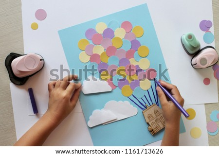 Cute little 5-6 years old girl making crafted applied ornament with colored paper and wooden house, decorative punchers and color paper to create fun and easy with children, concept for kindergarten
