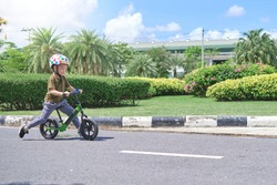 Cute little 4 years old toddler boy child wearing safety helmet learning to ride first balance bike (run bike) in sunny summer day, Kid cycling, playing outside at park, Fun exercise for kids concept