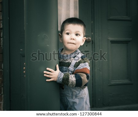 Cute lonely boy standing and leaning on a green pole, vintage photograph taken in the street.