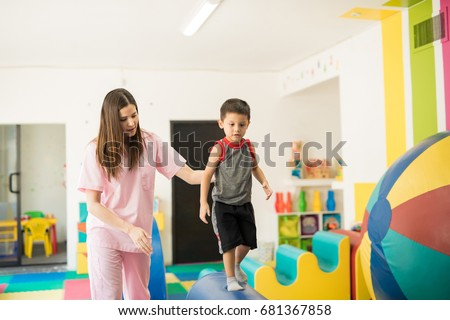 Cute looking boy walking on a beam to practice his balance with the help of a children physical therapist