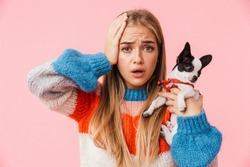 Cute lovely confused girl playing with her pet chihuahua isolated over pink background