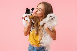 Cute lovely girl playing with her pet chihuahua and lapdog isolated over pink background