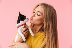 Cute lovely girl playing with her pet chihuahua isolated over pink background