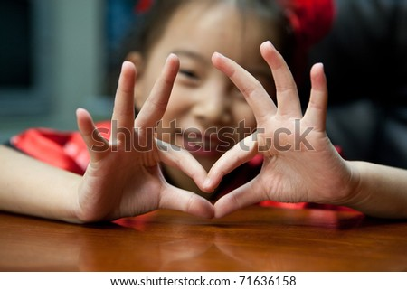 cute lovely sweet asian kid girl with love symbol in home background