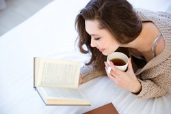 Cute lovely young woman reading book and drinking coffee on bed