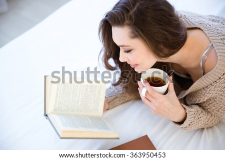 Shutterstock Cute lovely young woman reading book and drinking coffee on bed