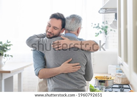 Cute loving caring old elderly senior father embracing hugging his adult caucasian son in the kitchen while cooking lunch, dinner, preparing meal together. Happy father`s day! I love you, dad!