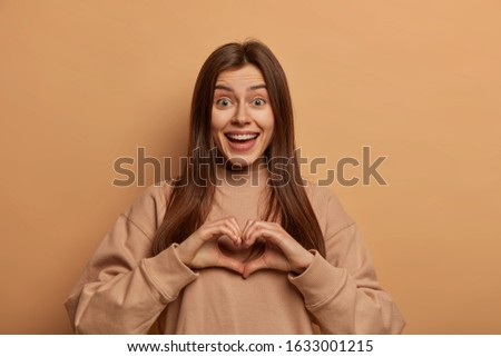 Cute loving woman expresses passion, affection and romantic mood to boyfriend, shapes heart gesture, spreads love and smiles gladfully, wears brown sweatshirt, poses in studio over beige wall