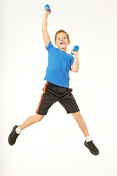 Cute male child holding dumbbells and jumping