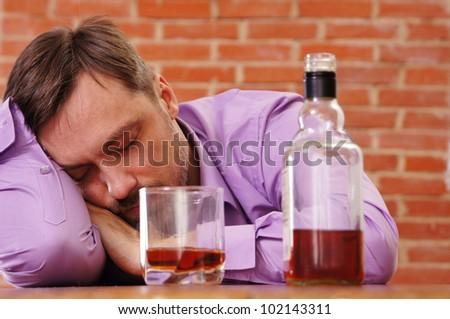 cute man drinking whiskey at brick wall