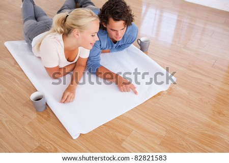 Cute man showing a point on a plan to his fiance while lying on the floor
