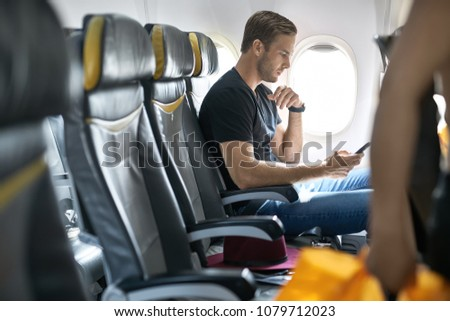Cute man sits in the airplane next to the window and holds a cellphone in the hands. He wears a black T-shirt with blue jeans. There is a crimson hat on a seat near him. Horizontal.